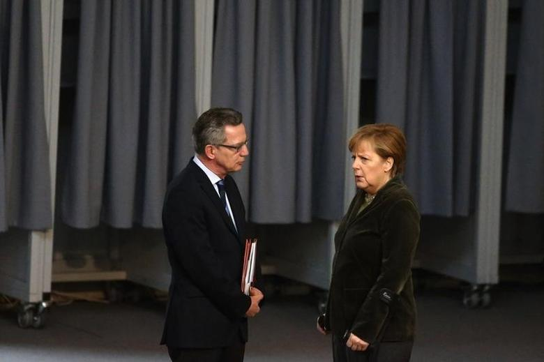 German Chancellor Angela Merkel (R) talks with Interior Minister Thomas de Maiziere before a session of the lower house of parliament, the Bundestag, in Berlin February 20, 2014. REUTERS/Thomas Peter