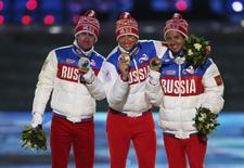 Russia's gold medallist Alexander Legkov poses with compatriots silver medallist Maxim Vylegzhanin (L) and bronze medallist Ilia Chernousov (R) after being presented with medals for the men's cross-country 50km mass start free event during the closing ceremony of the 2014 Sochi Winter Olympics, February 23, 2014. REUTERS/Phil Noble