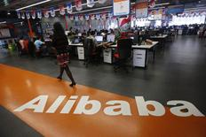 An employee walks past a logo of Alibaba Group at its headquarters on the outskirts of Hangzhou, Zhejiang province, in this May 17, 2010 file photo. REUTERS/Stringer