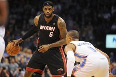 Feb 20, 2014; Oklahoma City, OK, USA; Miami Heat small forward LeBron James (6) handles the ball against Oklahoma City Thunder point guard Russell Westbrook (0) during the second quarter at Chesapeake Energy Arena. Mark D. Smith-USA TODAY Sports