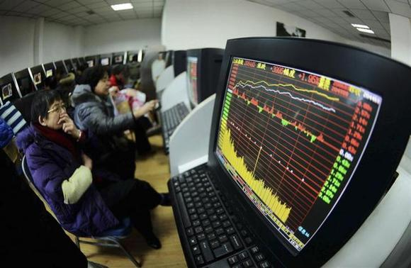 Investors look at computer screens displaying stock information at a brokerage house in Qingdao, Shandong province February 10, 2014. REUTERS/China Daily
