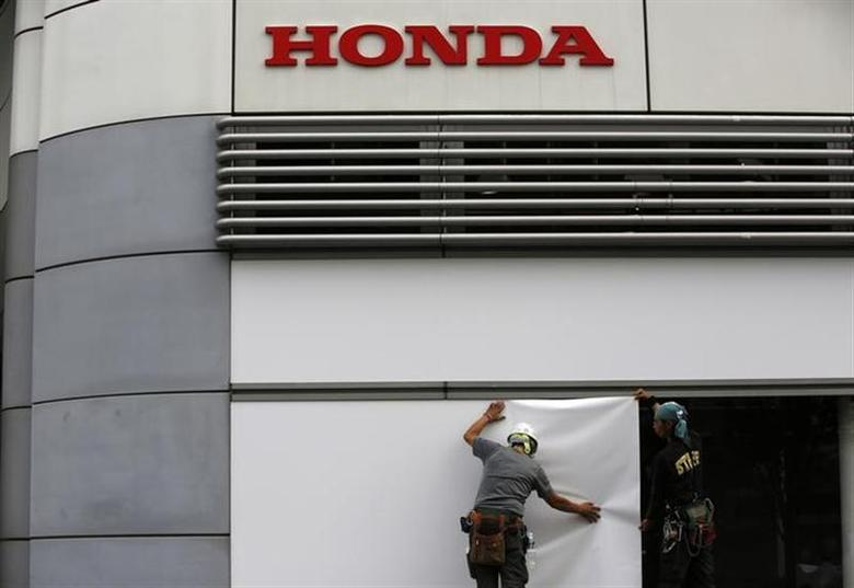 Workers stand under the logo of Honda Motor Co. outside the company's headquarters in Tokyo October 30, 2013. REUTERS/Issei Kato/Files