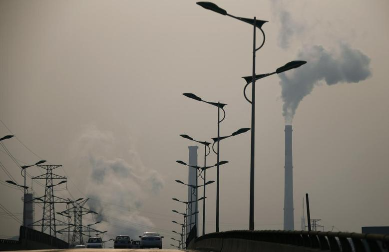 Smoke rises from chimneys of a steel plant next to a viaduct on a hazy day in Tangshan, Hebei province February 18, 2014. REUTERS/Petar Kujundzic