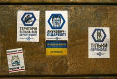 Стикеры на кузове сгоревшего грузовика у здания парламента в Киеве 23 февраля 2014 года. Исполняющий обязанности министра внутренних дел Украины Арсен Аваков сообщил, что отстраненный в субботу парламентом от должности президента и скрывшийся в неизвестном направлении Виктор Янукович объявлен в розыск. REUTERS/Baz Ratner