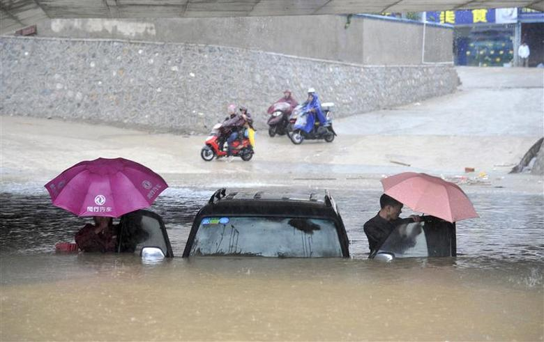 People get out of a stranded car at a flooded underpass amid heavy rainfalls under the influence of Typhoon Haiyan, in Nanning, Guangxi Zhuang autonomous region November 11, 2013. REUTERS/China Daily