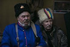 Казаки сидят у своей палатки на Майдане Незалежности в Киеве 23 февраля 2014 года. Украина, пережившая на прошлой неделе масштабное кровопролитие и смену власти, надеется сохранить скидку на импортируемый из России газ, который подешевел для Киева с конца прошлого года. REUTERS/Baz Ratner