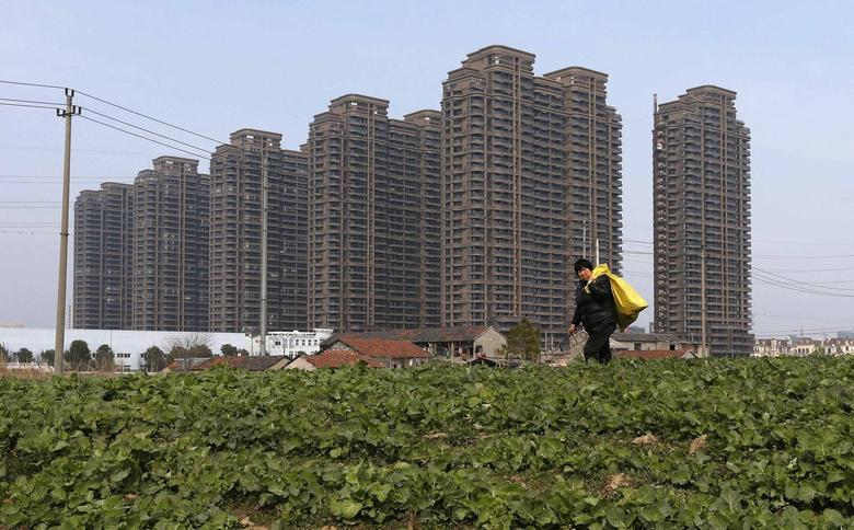 A farmer walks past a vegetable field near newly-built residential buildings in Jiaxing, Zhejiang province February 23, 2014. REUTERS/William Hong