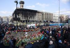 Люди оставляют цветы на баррикадах в Киеве в память о погибших, 24 февраля 2014 года. Украина, сменившая власть в результате революции, которая унесла десятки жизней, объявила в международный розыск свергнутого президента Виктора Януковича и сообщила в понедельник, что государственная казна пуста. REUTERS/David Mdzinarishvili