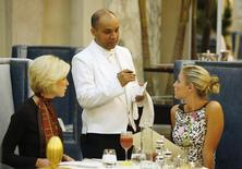 """Waiter Sayed Islam (C) speaks with Kelley Ruland (R) and Brittany Parker in """"The Plaza"""" hotel's """"Palm Court"""" the first day that the hotel re-opened following extensive renovations in New York March 1, 2008. REUTERS/Lucas Jackson"""