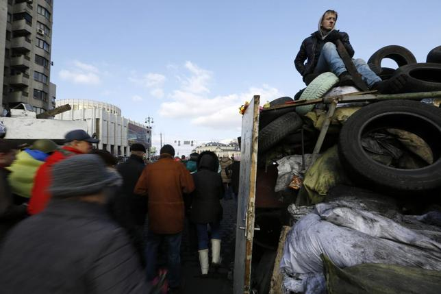 An anti-Yanukovich protester sits atop a barricade in Kiev's Independent Square February 24, 2014. REUTERS/Yannis Behrakis