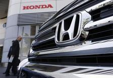 Unos visitantes observan un vehículo de Honda a las afueras del salón de exhibiciones de la firma en Tokio, abr 26 2013. La automotriz Honda Motor Co realizó el lunes dos inéditos nombramientos, al designar por primera vez a una mujer en su junta directiva y a un brasileño como jefe de operaciones, en un intento por ponerse al día frente a sus rivales locales en la diversificación de sus filas ejecutivas. REUTERS/Yuya Shino