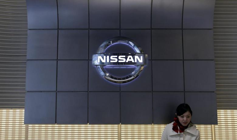 A staff stands near the logo of Nissan Motor at the company's showroom in Tokyo February 10, 2014. REUTERS/Toru Hanai