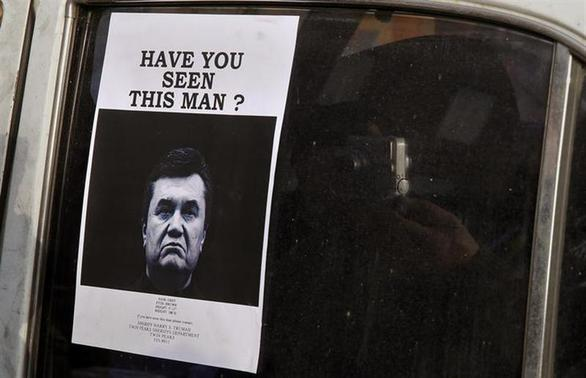 A man takes photos of a 'Wanted' notice, of fugitive Ukrainian President Victor Yanukovich, plastered on the window of a car used as barricade near Kiev's Independent Square February 24, 2014. REUTERS/Yannis Behrakis
