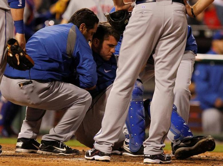 New York Mets catcher Josh Thole is helped to his feet after a collision at home plate with the Philadelphia Phillies Ty Wigginton (unseen) during the eighth inning of their National League MLB baseball game in Philadelphia, Pennsylvania, May 7, 2012. REUTERS/Tim Shaffer