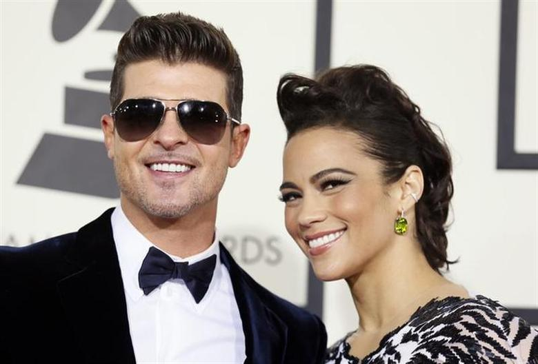 Singer Robin Thicke and wife, actress Paula Patton, arrive at the 56th annual Grammy Awards in Los Angeles, California January 26, 2014. REUTERS/Danny Moloshok/Files