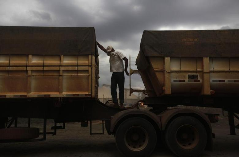 A Brazilian truck driver covers his face to protect himself from dust as he waits to unload his cargo of cereal grain at the rail terminal of America Latina Logistica (ALL), along highway BR-364 in Alto de Araguaia, Mato Grosso state September 24, 2012. REUTERS/Nacho Doce