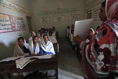 A teacher displays a flash card to students while describing preventive measures to take when sexual harassment occurs, during a class in Shadabad Girls Elementary School in Pir Mashaikh village in Johi, some 325 km (202 miles) from Karachi February 12, 2014. REUTERS/Akhtar Soomro