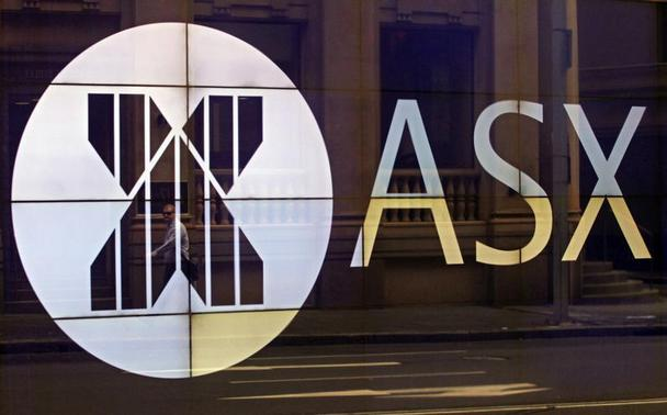 An office worker walks past the board of the Australian Securities Exchange building displaying its logo in central Sydney April 5, 2013. REUTERS-Daniel Munoz