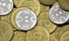 Принадлежащие энтузиасту Bitcoin монеты в его офисе в Сэнди, штат Юта, 31 января 2014 года. Киберпреступники заразили сотни тысяч компьютеров вирусом под названием Pony для кражи биткоинов и других цифровых валют, совершив самую смелую из известных на данный момент атак с целью завладеть чужими электронными деньгами, сообщила фирма Trustwave. REUTERS/Jim Urquhart