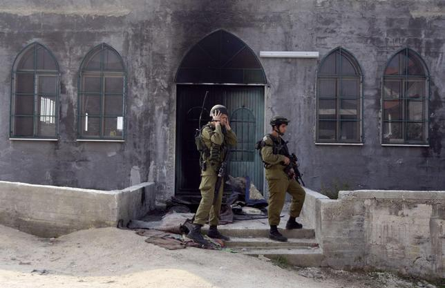 Israeli soldiers stand near the damaged door of a mosque, set ablaze by vandals, in the West Bank village of Urif, near Nablus in this November 19, 2012 file photo. REUTERS/Abed Omar Qusini/Files