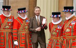 British cyclist Bradley Wiggins poses for a photograph with his Knighthood medal, and Yeomen of the Guard, awarded to him by Queen Elizabeth during an Investiture ceremony at Buckingham Palace in central London December 10, 2013. REUTERS/John Stillwell/Pool
