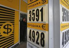 Мужчина выходит из пункта обмена валют в Москве 20 февраля 2014 года. Рубль в минусе на торгах вторника в основном из-за неблагоприятных внешних факторов и несмотря на последний день уплаты налога на добычу полезных ископаемых, под который обычно увеличивается продажа экспортной валютной выручки. REUTERS/Maxim Shemetov