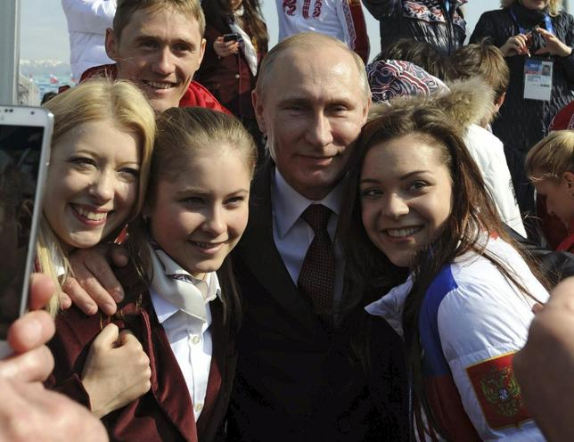 Russian President Vladimir Putin (C) and Russian Olympic medal winning athletes pose for a picture in Sochi February 24, 2014. REUTERS/Mikhail Klimentyev/RIA Novosti/Kremlin