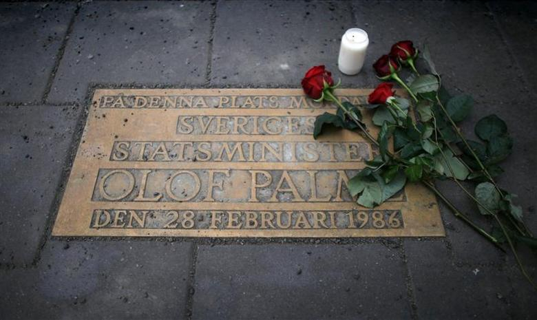 Roses are laid on a plaque marking the location where Swedish Prime Minister Olof Palme was shot and killed on a street in Stockholm February 28, 2011. REUTERS/Bob Strong