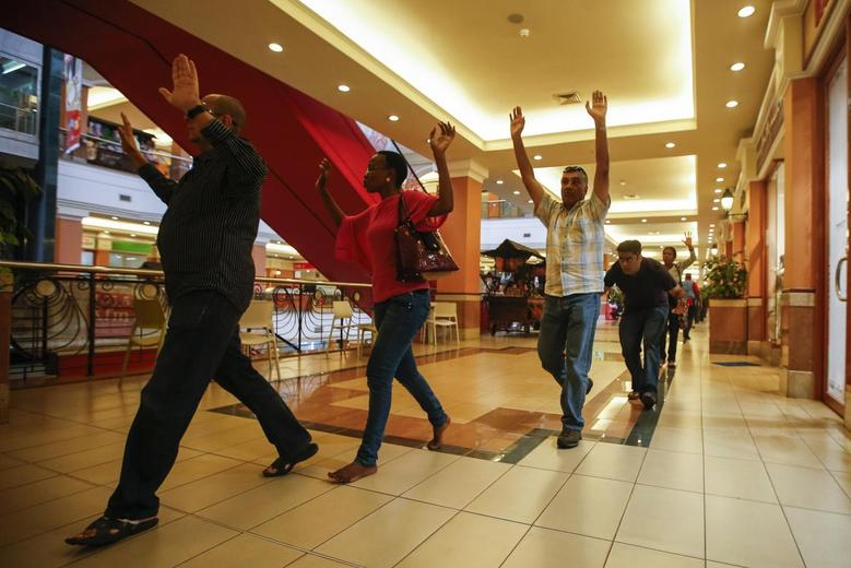 Shoppers and shop assistants raise their hands as they are escorted to safety while armed police hunt for gunmen who went on a shooting spree in Westgate Shopping Centre in Nairobi, Kenya September 21, 2013. REUTERS/Goran Tomasevic