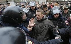 Полиция задерживает оппозиционного лидера Алексея Навального в Москве 24 февраля 2014 года. Навальный во вторник приговорён к административному аресту на семь суток за сопротивление задержанию в ходе акции протеста против приговора активистам, получившим накануне сроки за столкновения с полицией на демонстрации перед очередным вступлением Владимира Путина в должность президента в 2012 году. REUTERS/Tatyana Makeyeva