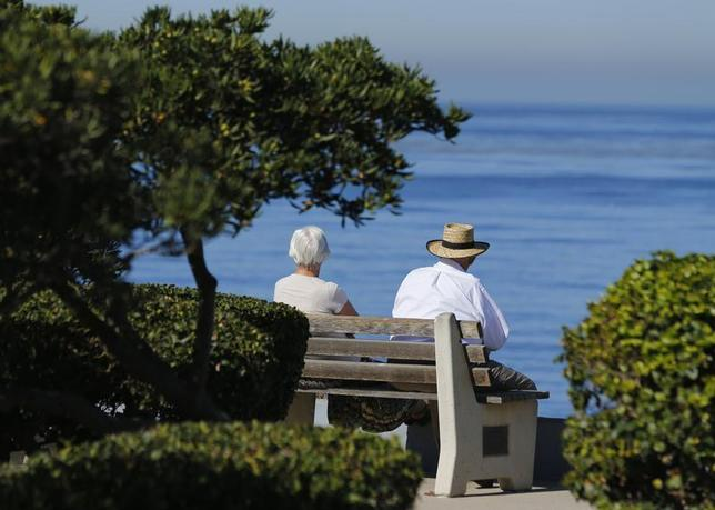 An elderly couple looks out at the ocean as they sit on a park bench in La Jolla, California November 13, 2013. REUTERS/Mike Blake