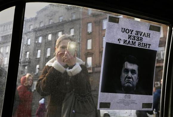 A woman takes photos of a ''Wanted'' notice for fugitive Ukrainian President Victor Yanukovich, plastered on the window of a car used as a barricade, near Kiev's Independent Square February 24, 2014. REUTERS/Yannis Behrakis