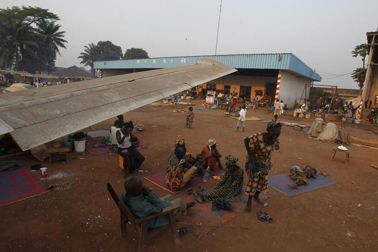 A family displaced by inter-communal violence in the country sit near a plane in a camp for displaced persons at Bangui M'Poko International Airport February 20, 2014. REUTERS/Luc Gnago