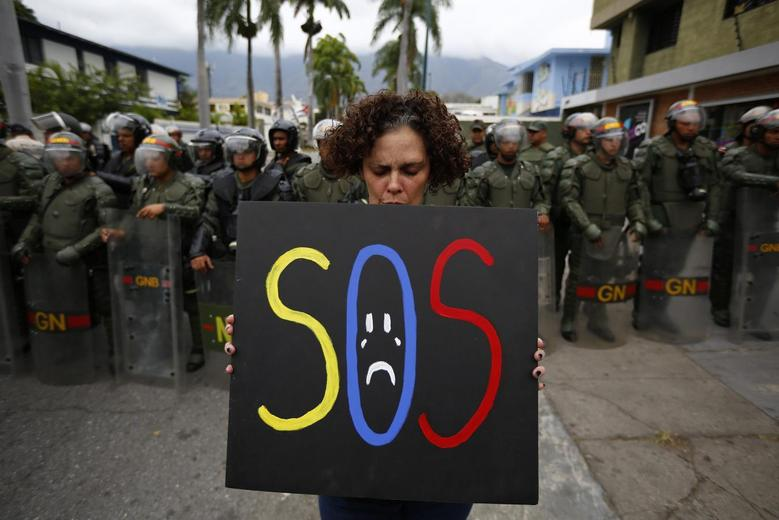 A demonstrator holds a placard as she stands in front of national guards during a protest near the Cuba's Embassy in Caracas February 25, 2014 file photo. REUTERS/Jorge Silva