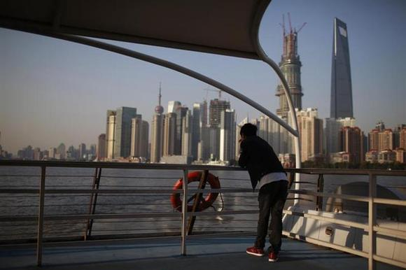 A man stands on a boat on the Huangpu River near the Pudong Lujiazui financial area in Shanghai November 12, 2012. REUTERS/Aly Song/Files