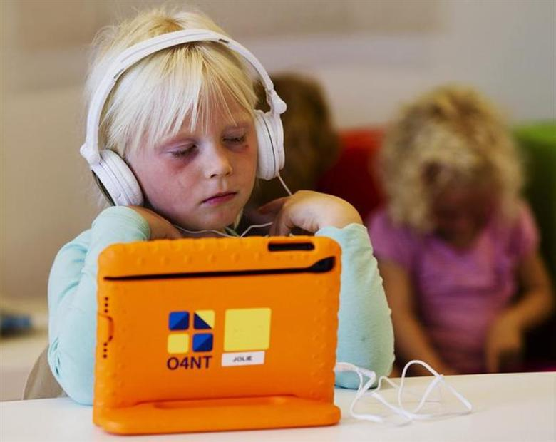 A girl listens to music on her iPad at the Steve Jobs school in Sneek August 21, 2013. REUTERS/Michael Kooren/Files
