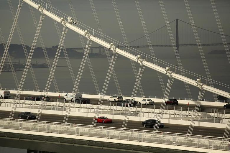 The Golden Gate Bridge is seen in the background as vehicles travel on the new east span of the San Francisco Oakland Bay Bridge in Oakland, California November 12, 2013. REUTERS/Robert Galbraith