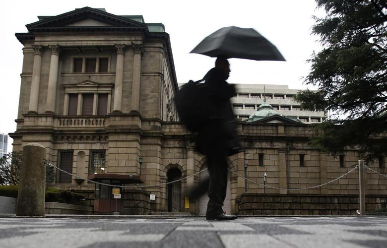 A pedestrian holding an umbrella to take shelter from rain and hail walks past the Bank of Japan headquarters building in Tokyo December 20, 2013. REUTERS/Yuya Shino