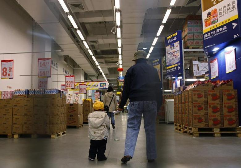 A customer walks with a child inside a wholesale retailer store in Beijing December 4, 2010. REUTERS/Petar Kujundzic