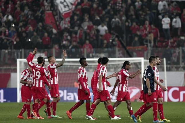 Olympiakos' players celebrate their victory over Manchester United after their Champions League round of 16 first leg soccer match at Karaiskaki stadium in Piraeus, near Athens, February 25, 2014. REUTERS/Alkis Konstantinidis