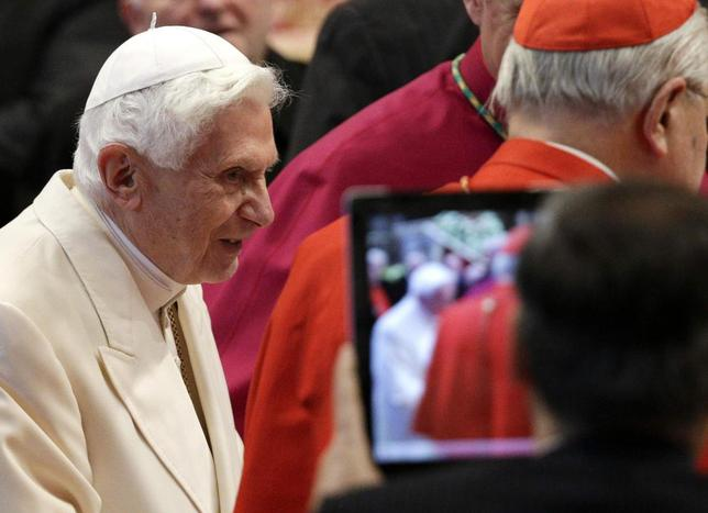 A faithful takes a picture as former pope Benedict XVI arrives for a consistory ceremony led by Pope Francis in Saint Peter's Basilica at the Vatican February 22, 2014. REUTERS/Max Rossi