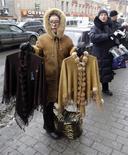 Женщины продают одежду на улице Санкт-Петербурга 26 февраля 2009 года. Потребительские цены в России с 18 по 24 февраля вновь выросли на 0,2 процента, как и в предыдущие две недели, а с начала месяца рост цен превысил показатель всего февраля 2013 года, сообщил Росстат. REUTERS/Alexander Demianchuk