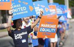 Keri Bias (L) holds a sign in support of same sex marriage in front of the Hawaii State Capital in Honolulu in this file photo taken October 28, 2013. REUTERS/Hugh Gentry/Files