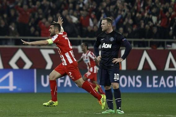 Olympiakos' Giannis Maniatis (L) celebrates a goal as Manchester United's Wayne Rooney (R) reacts during their Champions League round of 16 first leg soccer match against Manchester United at Karaiskaki stadium in Piraeus, near Athens, February 25, 2014. REUTERS/Alki