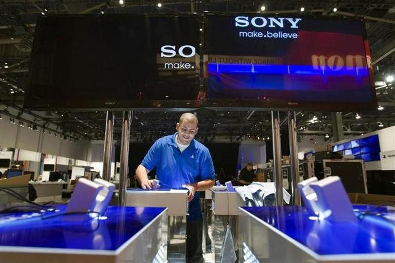 Alex Belfield, an event planner for Sony PlayStation, prepares a display for the PlayStation Vita as workers prepare for the 2012 International CES at the Las Vegas Convention Center in Las Vegas, Nevada, January 8, 2012.REUTERS/Steve Marcus/Files