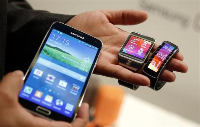 The new Samsung Galaxy S5 smartphone (L), Gear 2 smartwatch (C) and Gear Fit fitness band are displayed at the Mobile World Congress in Barcelona February 23, 2014. REUTERS/Albert Gea