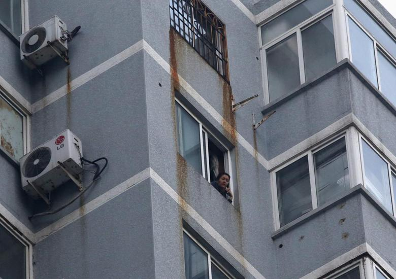 Guzailai Nu'er, the wife of Ilham Tohti, speaks as she has an interview with Reuters by a phone from window of her house in Beijing, January 17, 2014. REUTERS/Kim Kyung-Hoon
