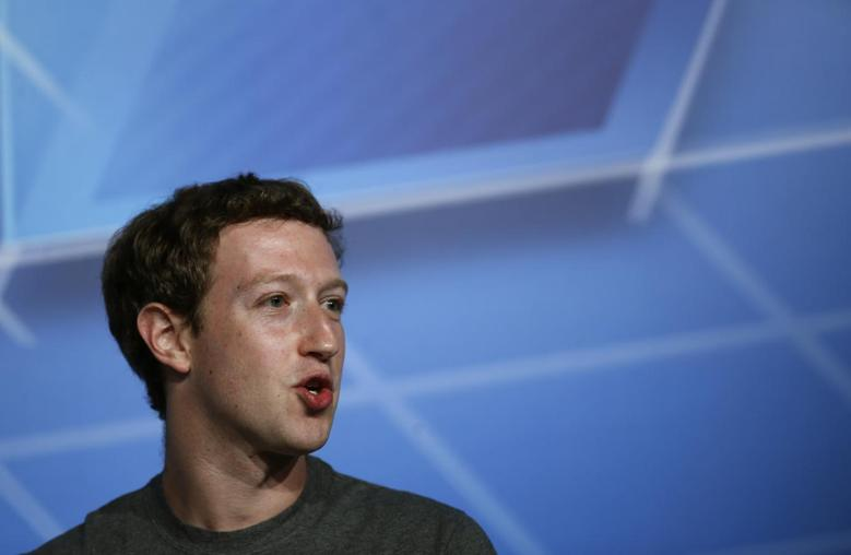 Facebook Chief Executive Officer Mark Zuckerberg smiles in the stage before delivering a keynote speech during the Mobile World Congress in Barcelona February 24, 2014. REUTERS/Albert Gea