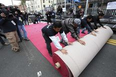 Workers roll out the Oscars red carpet during preparations for the 86th Annual Academy Awards in Hollywood, California February 26, 2014. REUTERS/Jonathan Alcorn