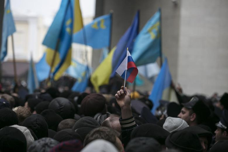 An ethnic Russian Ukrainian holds a Russian flag as Crimean Tatars rally near the Crimean parliament building in Simferopol February 26, 2014 file photo. REUTERS/Baz Ratner